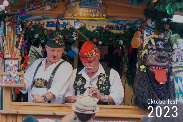 Männer verkaufen Holzpfeilen und Wasserpfeifen in bayrischer Tracht an einer kleinen Bude, neben dem Bildtitel Oktoberfest 2023