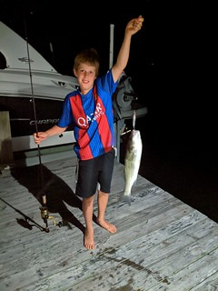 Photo of boy with striped bass he caught