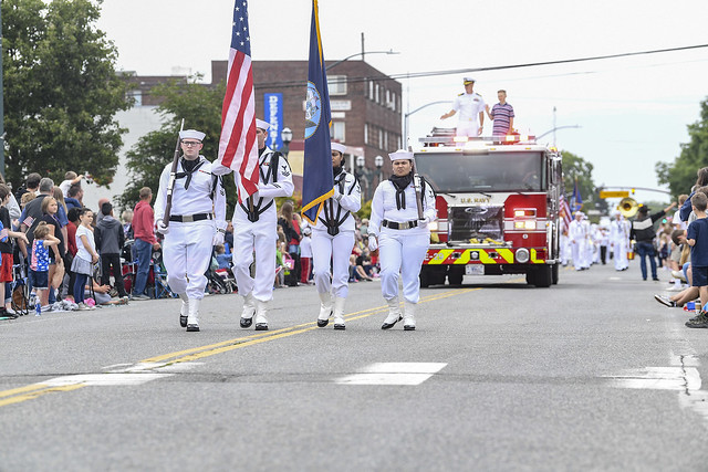 Members of the Naval Station Everett Honor Guard lead a military procession through the streets of downtown Everett, Washington during the 4th of July parade.