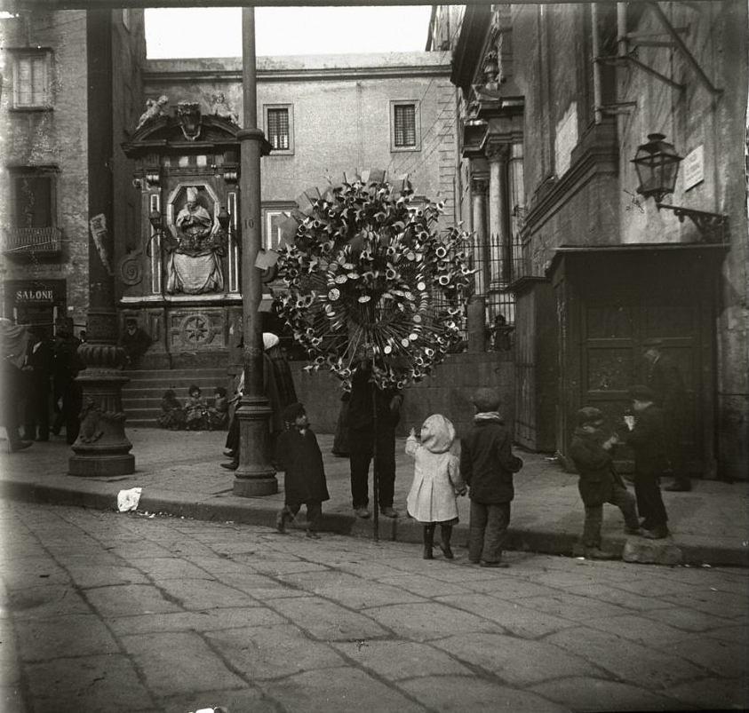 1909. Италия. Неаполь. Продавец разноцветных вертящихся игрушек и его покупатели в предрождественский день