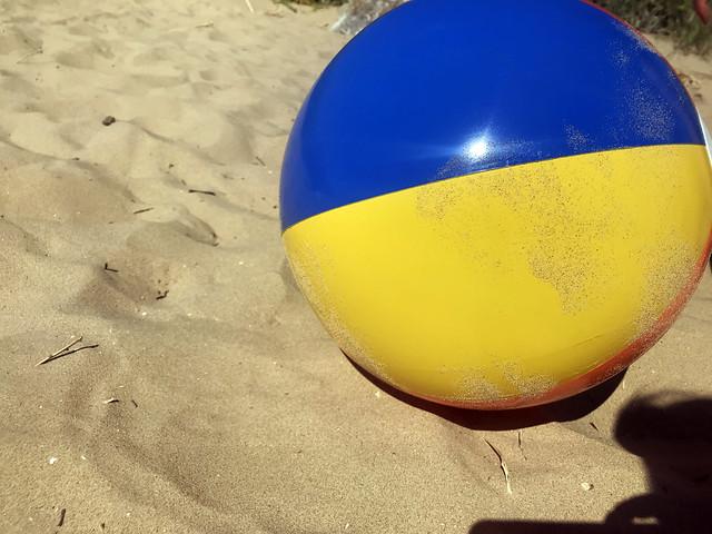 Coloured beach ball in the sand. Summer stock photo.