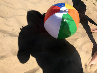 Beach ball bouncing on the sand in summer, stock photo