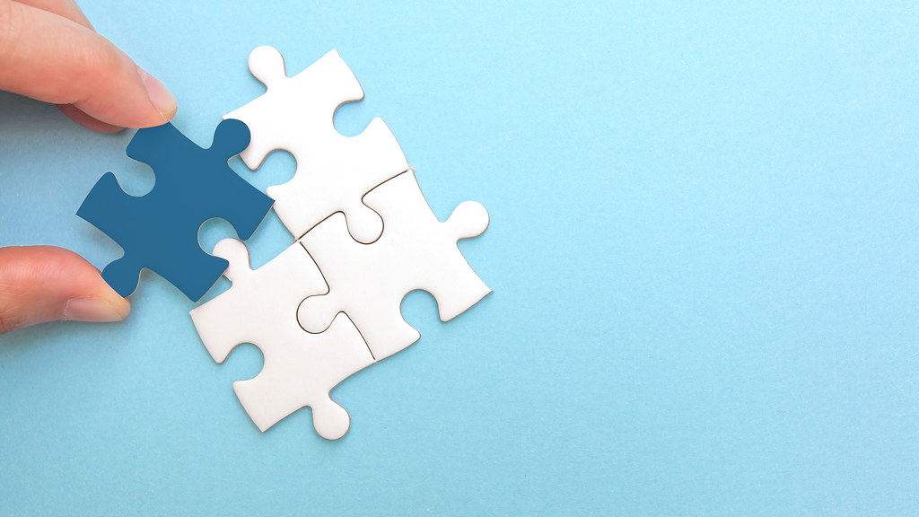 Graphic showing a white jigsaw puzzle on a blue background. One of the pieces is upturned to show it's dark blue underside.