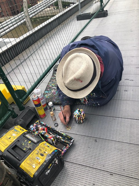 A man in straw hat leaning over while he paints on a steel bridge.