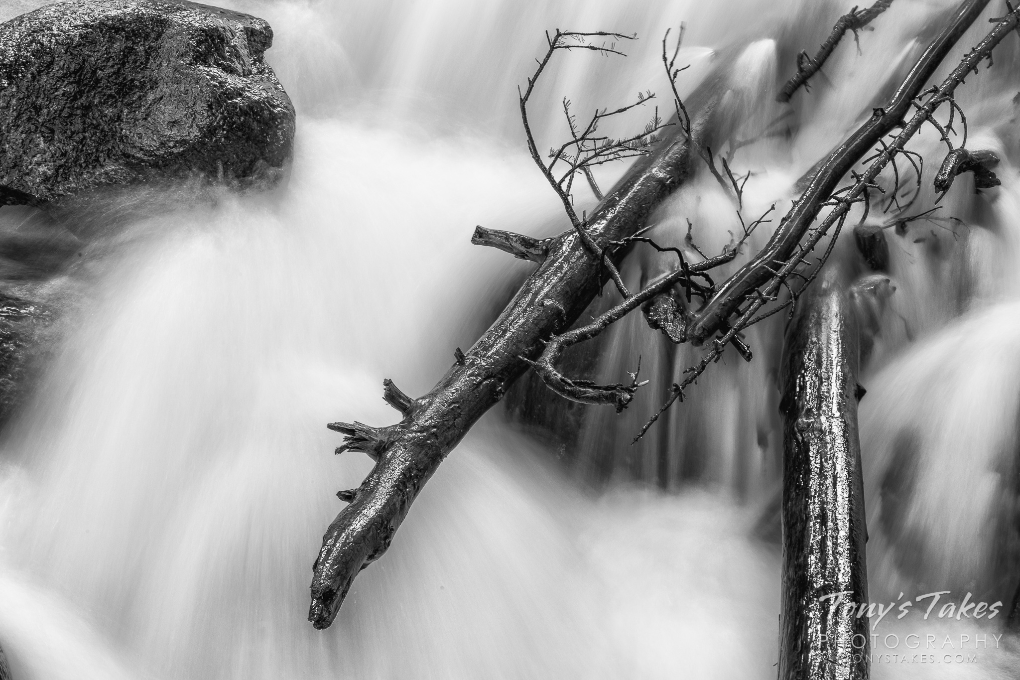 Motion-blurred waters in a mountain creek rush by fallen logs. (© Tony's Takes)