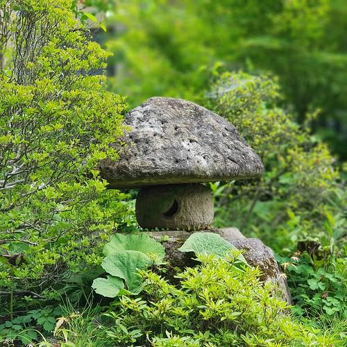 Eine Steinlaterne, die einem Waldpilz nachempfunden ist