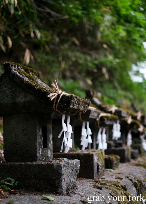 Row of tiny stone shrines at Kumanokoutai Jinja Shrine in Karuizawa featured on Terrace House Opening New Doors