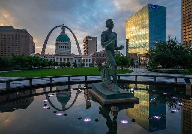 The running man statue and the famous arch at St Louis, Missouri during sunrise.