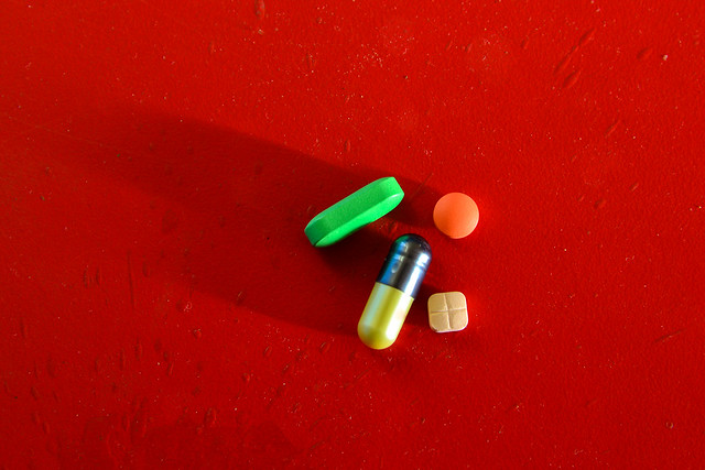 Medical or vitamin pills on red background