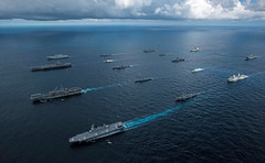 CORAL SEA (July 11, 2019) The amphibious assault ship HMAS Canberra (L 02), top left, the aircraft carrier USS Ronald Reagan (CVN 76), top center-left, the amphibious assault ship USS Wasp (LHD 1), bottom center-left, and the Japanese helicopter destroyer JS Ise (DDH 182), bottom left, sail in formation with 13 other ships from the U.S. Navy, U.S. Coast Guard, Royal Australian Navy, Royal Canadian Navy and Japan Maritime Self-Defense Force (JMSDF) during Talisman Sabre 2019. Talisman Sabre illustrates the closeness of the Australian and U.S. alliance and the strength of the military-to-military relationship. It is the eighth iteration of this exercise. (U.S. Navy photo by Mass Communication Specialist 2nd Class Kaila V. Peters)