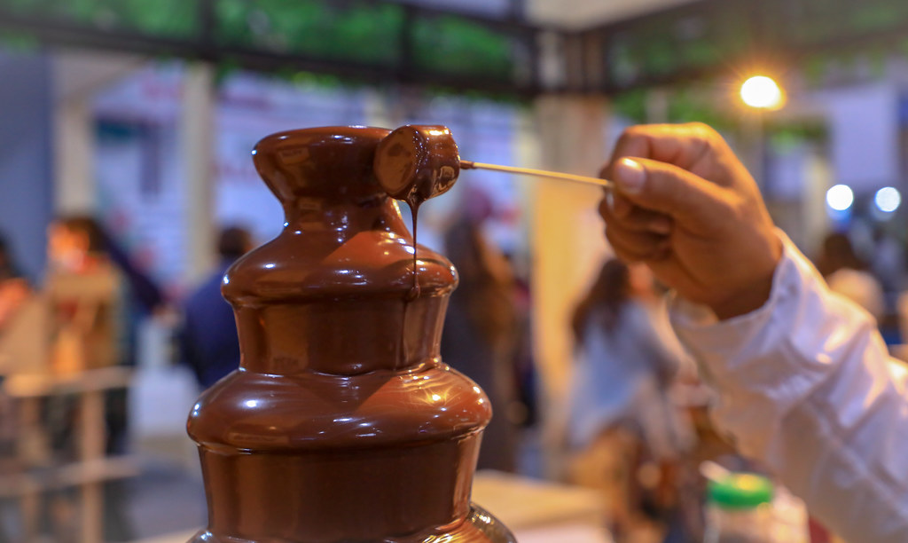 Marshmallow on a stick being put into a chocolate fountain