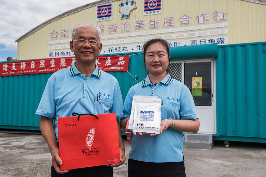 漁權會合作社理事主席王惠生(左)拿著招牌禮盒,創社就加入營運團隊的文書郭雅郁(右)拿著主婦聯盟合作社客製的虱目魚鬆。