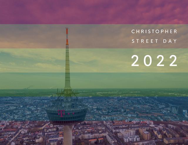 Luftbildaufnahme der Kölner Sehenswürdigkeit Colonius, neben dem Bildtitel Christopher Street Day 2022