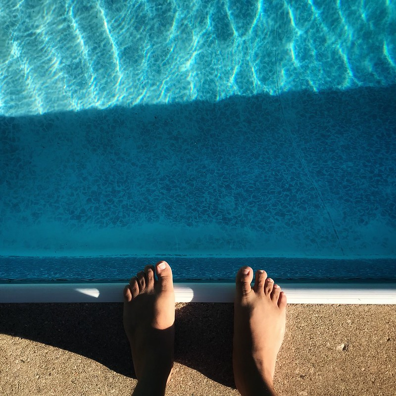Feet on the edge of a swimming pool