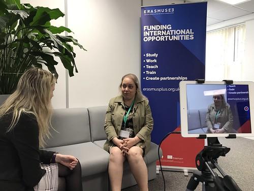 Interviewer and interviewee, with Erasmus+ banner in background