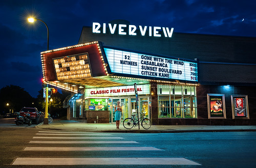 riverviewtheater cinema movie artdeco minneapolis saintpaul minnesota mn neighborhood streamlinemoderne architecture style film picture show pictureshow filmfestival classicmovies gonewiththewind casablanca sunsetboulevard citizenkane goldenage hollywood street light crossing crosswalk night girl popcorn posters marquee sign classic bike bicycle bluehour