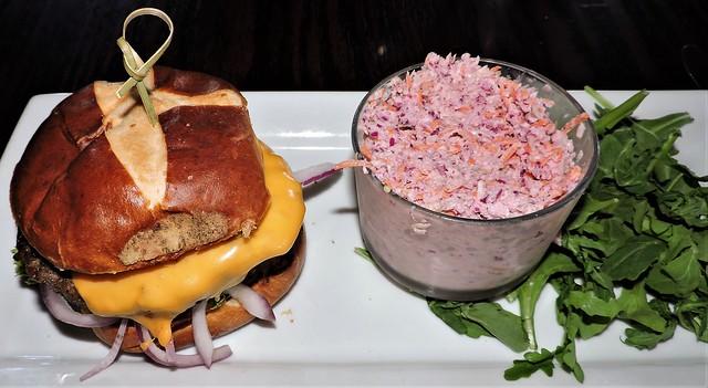 Burger with onions, cheddar, horseradish cream, on a pretzel bun; purple cabbage coleslaw; arugula