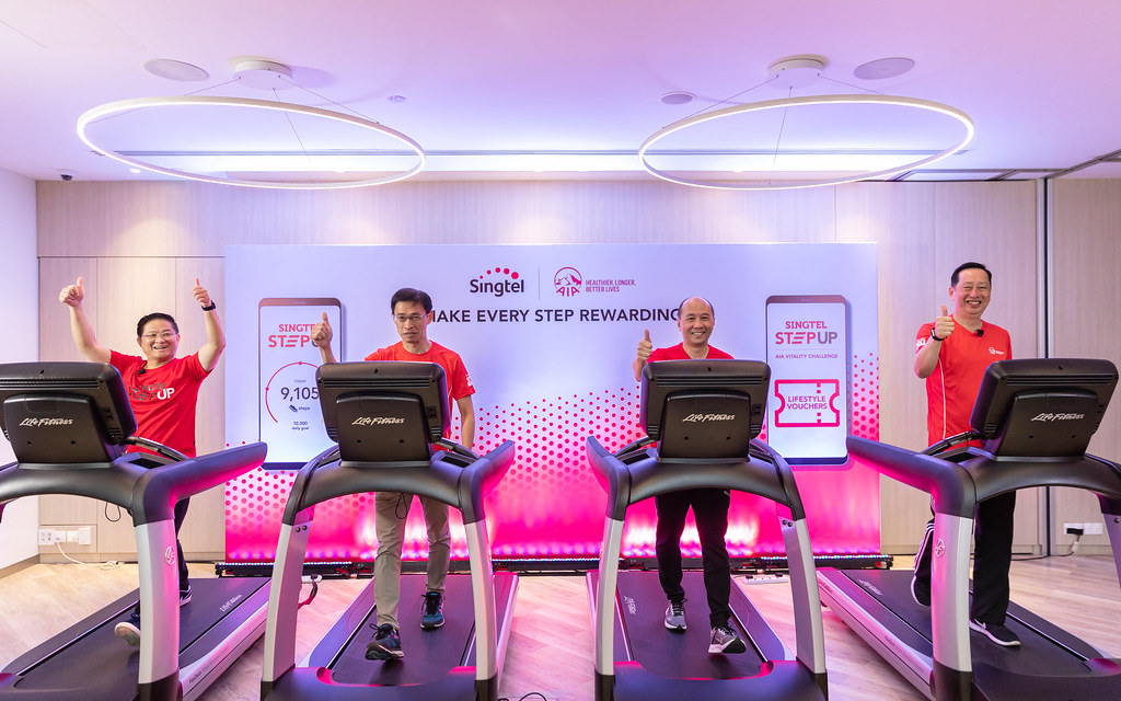 From left: Mr Wong Soon Nam, VP, Consumer Products, Consumer Singapore at Singtel, Mr Tan Hak Leh, Regional CEO of AIA Group, Mr Yuen Kuan Moon, CEO of Consumer Singapore at Singtel and Mr Patrick Teow, CEO of AIA Singapore walking on treadmills to officially launch StepUp