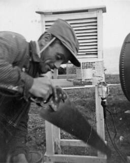 A man uses a saw at a construction site for a new building, Cap-de-la-Madeleine, Quebec / Un homme manie une scie sur le chantier de construction d'un nouvel édifice, au Cap-de-la-Madeleine (Québec)