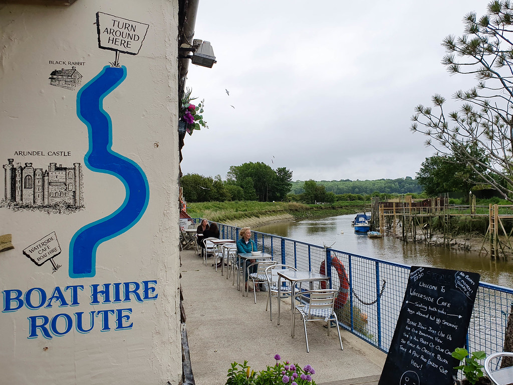 A boat hire sign next to the river