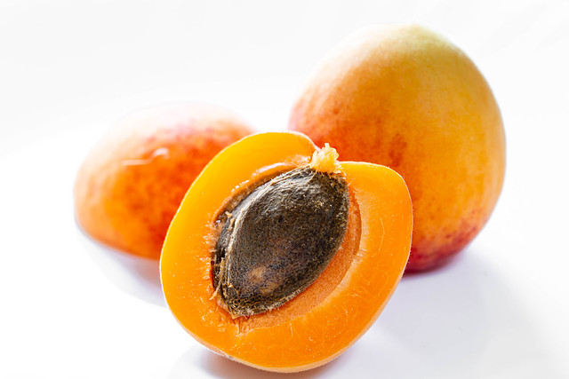 Whole apricot and halves on white background