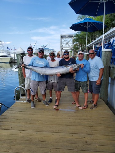 Photo of men holding 109-pound wahoo