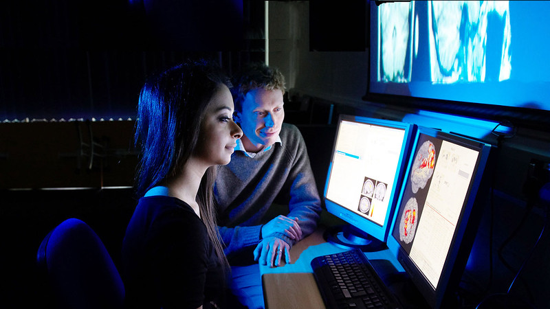 Male and female at in front of two computer screen with images of the brain