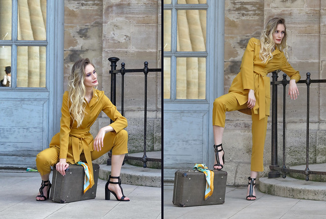 Blonde supermodel in a fixed pose with suitcase