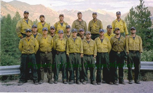 19 wildland firefighters in sooty yellow nomex shirts posing for a photo on  a roadside.