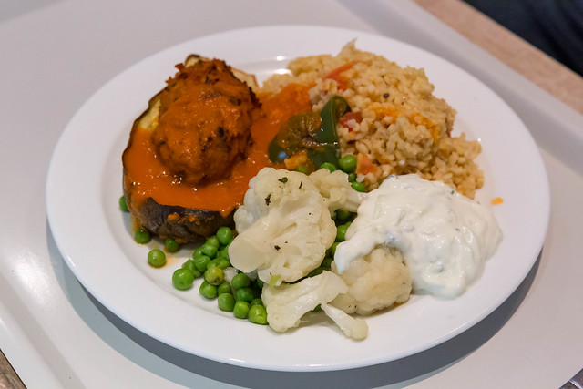 Vegan meal on white plate: Baked aubergine with soy, bulgur and colorful vegetables