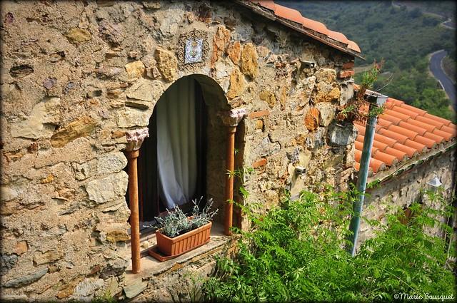 Jolie fenêtre de Castelnou avec cadran solaire et vue sur la route en lacets