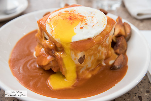 Francesinha - a tower of white bread filled with chorizo, house made pork sausage, slices of steak, slices of pork tenderloin topped with gooey cheese and sunny side egg smothered in tomato gravy and a side of baked potatoes