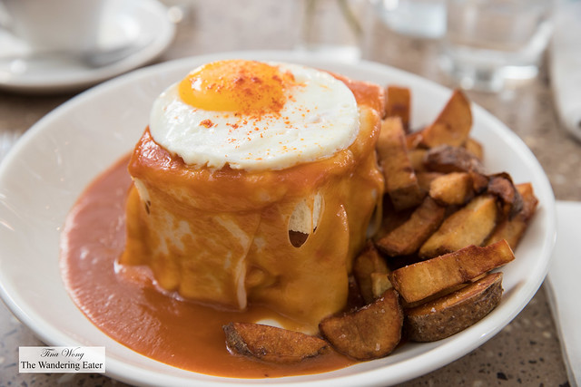 Francesinia - a tower of white bread filled with chorizo, house made pork sausage, slices of steak, slices of pork tenderloin topped with gooey cheese and sunny side egg smothered in tomato gravy and a side of baked potatoes