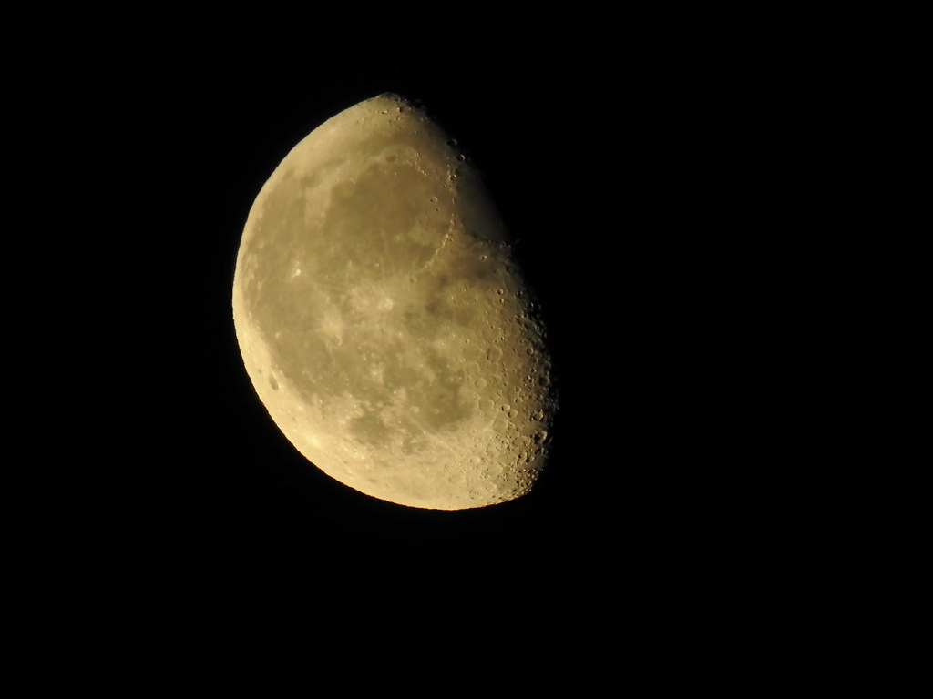 Moon, handheld against the window frame