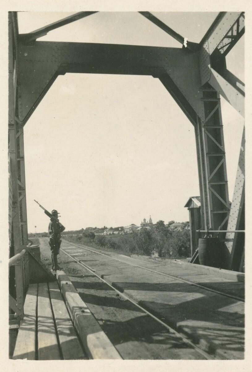 14. Охранник с винтовкой стоит рядом с железнодорожными путями.