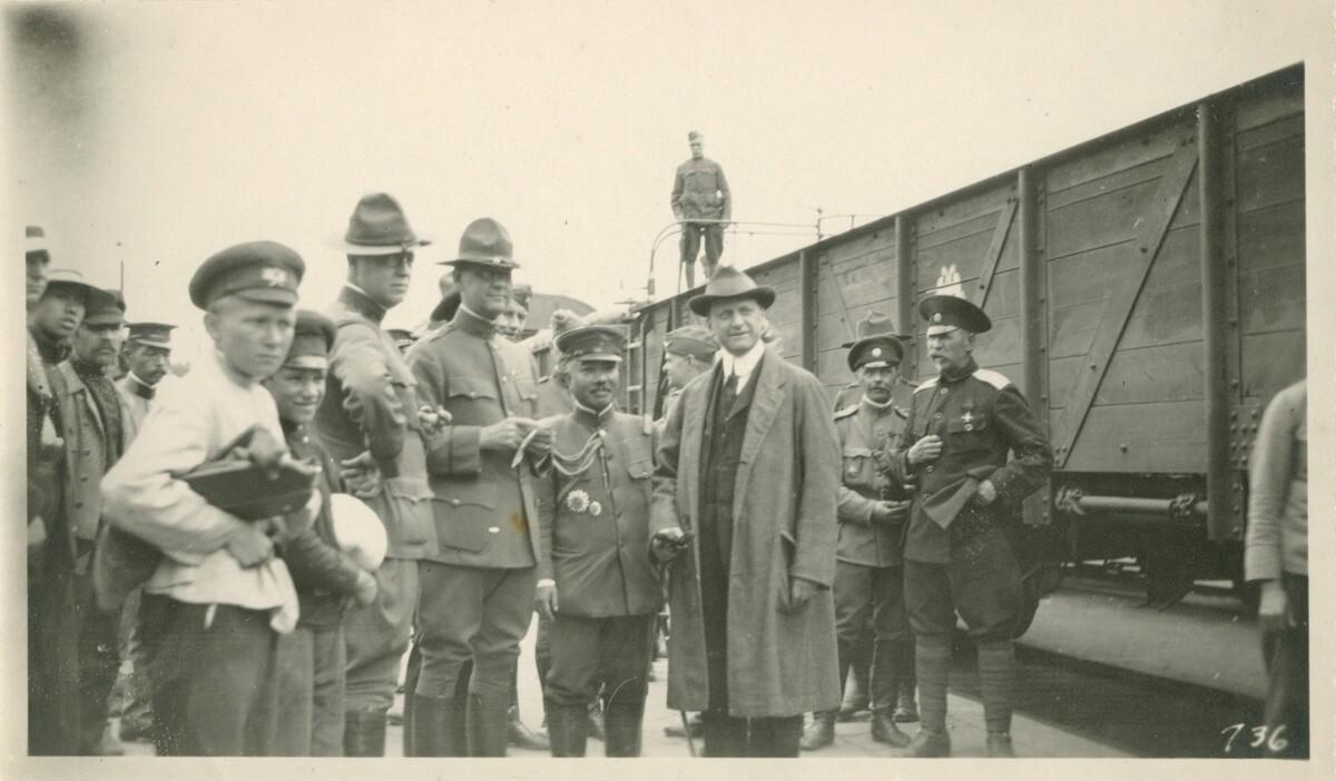 10. Роберт Эйчелбергер , военные чиновники в форме и другие мужчины стоят возле вагона поезда
