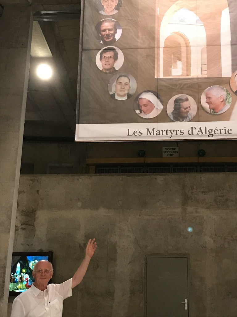 Canon Michael Brockie points to the banner commemorating the Algerian martyrs, including Blessed Christian Chessel.