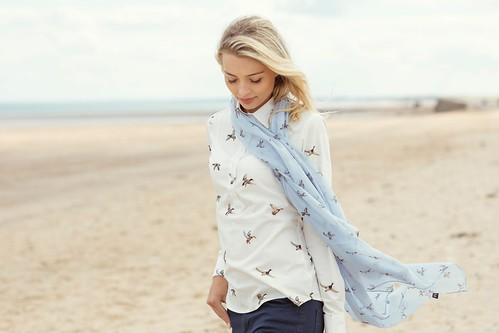 Woman in floaty printed scarf walking on the beach on a windy day