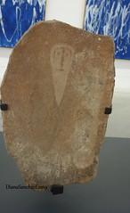 Roca decorada con un rostro o una mascara y un arma. 2000AC