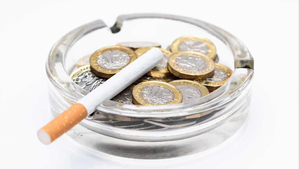 image of cigarette in ashtray with pounds coins inside
