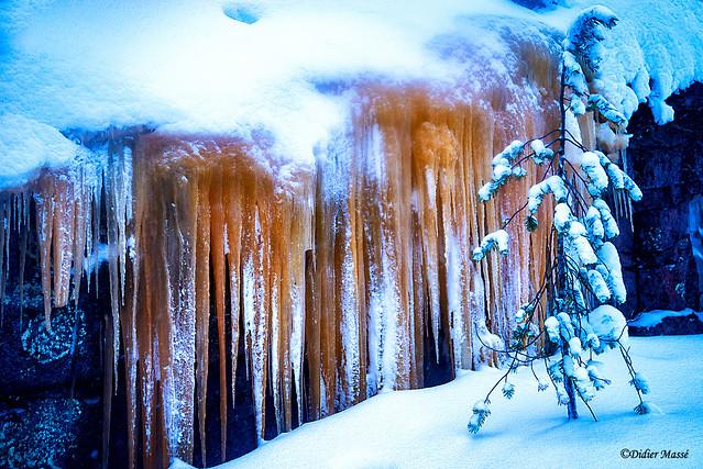 Stalagtites de glace sur un mur (la couleur rouge est due à un minerai de fer)