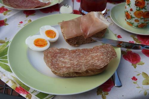 Baguettesalami und Serranoschinken auf Roggenbrot zu einem Ei von den neuen Hühnern von Freunden