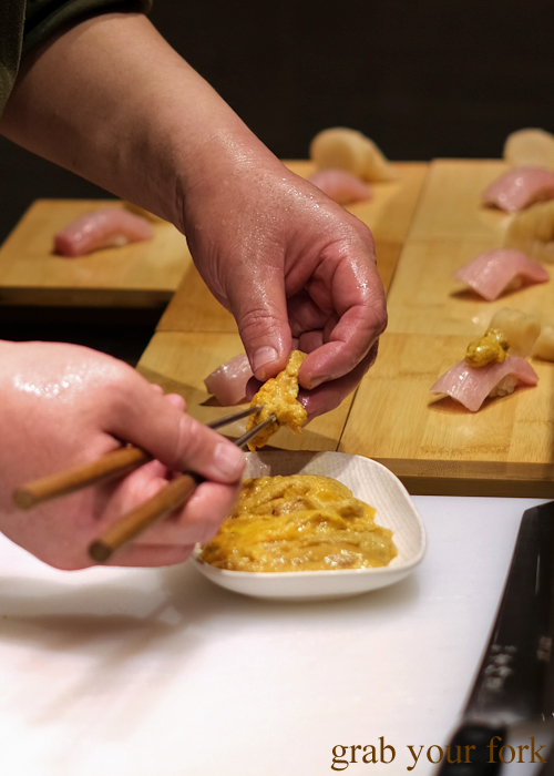 Chef Hideaki Fukada Adding uni sea urchin roe to ootoro nigiri sushi for our omakase at Jizakana in Cammeray, Sydney