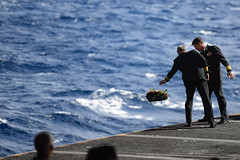 Capt. Pat Hannifin, commanding officer of USS Ronald Reagan (CVN 76), and Capt. Forrest Young, commanding officer of Carrier Air Wing (CVW) 5, lay a wreath into the Coral Sea during a remembrance ceremony, July 26. (U.S. Navy/MC3 Jason Tarleton)