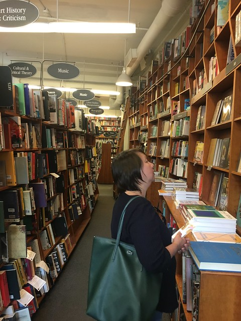 Harvard Book Store,  reading the book covers