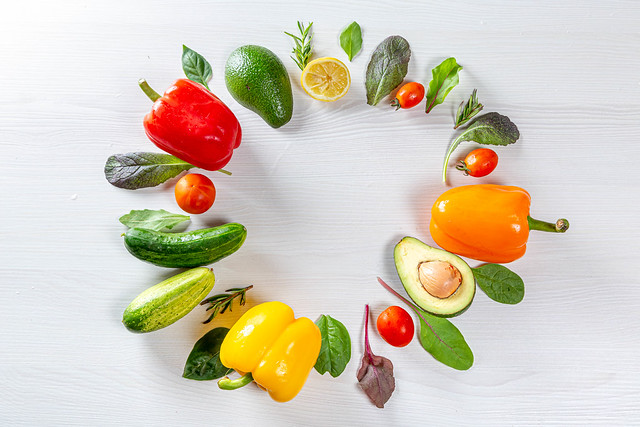 Fresh vegetables and greens are laid out in a circle on a white wooden background. Top view