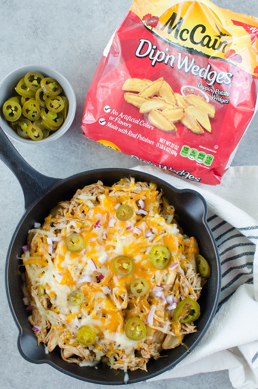 Pulled Pork Fries - crispy fries piled high with barbecue pulled pork, 2 kinds of cheeses, diced red onion, and jalapenos. Perfect for tailgating!
