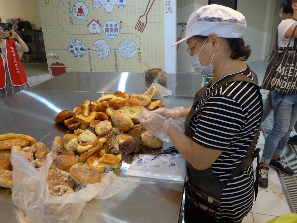 志工正在處理企業捐贈的食品,檢查品質、分裝、登記。孫文臨攝