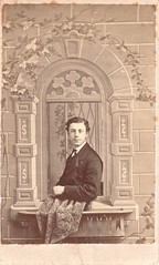 CDV_slightly smiling young man leaning out of an elaborate prop window, Chicago, Illinois