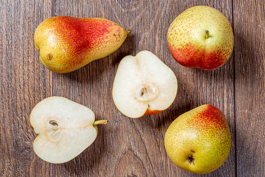 Whole ripe pears and halves on a wooden table. Top view | Flickr